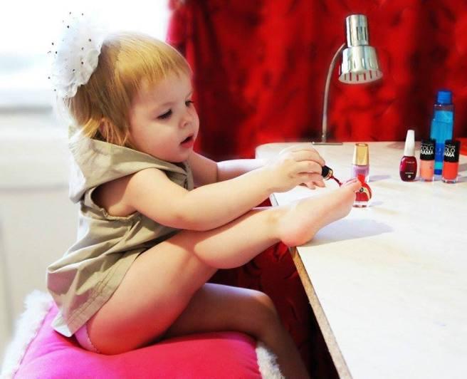 niña pintandose uñas pies