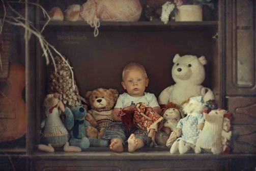niño entre muñecos